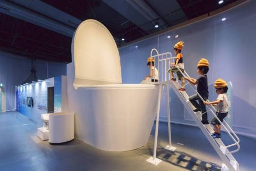 Children climbing into giant toilet