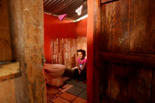 Keyla, 4, by her toilet in Bolivar, Ecuador. Photography Karla Gachet. Panos Pictures for WSUP.