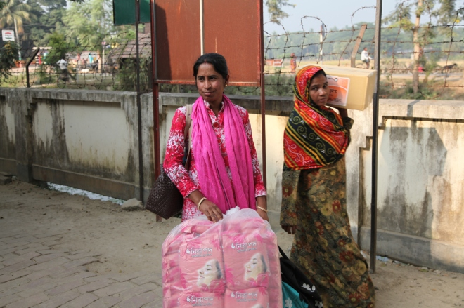 BRAC staff member (left) from Jessore district with sanitary napkins for schools.