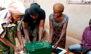 In Dodoma, Tanzania, a community group comes together every Saturday to organize their finances. Villagers earn interest on their savings and give out loans. Everyone plays a role - here three keyholders open the chest containing the loan registrations. Photograph: WSSCC/Jenny Matthews