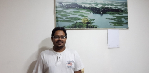 Dr. Ritesh Kumar standing in front of photo of Loktak Lake.
