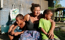 Elizabeth, 54, with two of her grandsons, Papua New Guinea.