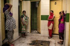 At a community toilet complex in Safeda Basti, one of Delhi's many slums, women wait their turn for the single functioning latrine—while covering their noses against the smell of feces left by someone who couldn't wait. Many people skip the hassle of city-run facilities altogether and do their business in rubble-strewn lots.