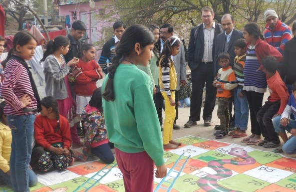Jesse Shapiro observes a life-size game of chutes and ladders, which illustrates the perils of poor sanitation and hygiene behaviors, on a field visit to an informal neighborhood in Delhi, India. Photo Credit: USAID